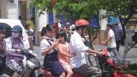 Two Vietnamese parents ride their children to school without crash helmets. Photo: Nhat Anh