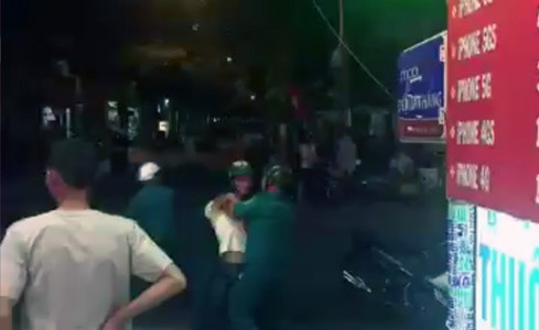 A still image from the clip showing a militiaman locking the arms of a man.