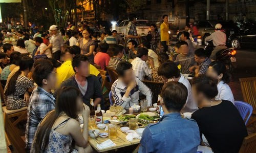 People drinking beer on the sidewalk in Ho Chi Minh City. Photo: Tri Quang