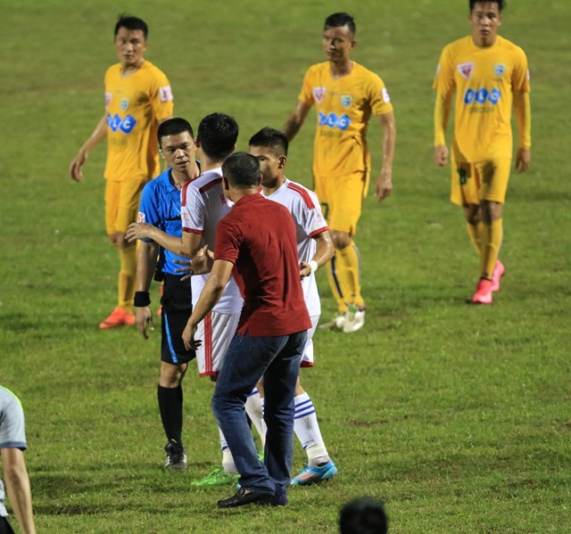 Song Lam Nghe An Coach Ngo Quang Truong (red) opposes the penalty decision of referee Ha Anh Chien. Photo: Minh Tu