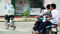Three high school students driving a motorbike without wearing crash helmet in Ho Chi Minh City. Photo: An Bang