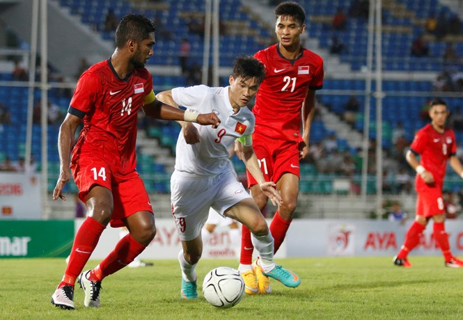 Vietnam's Cong Vinh (C) vies for the ball with two Singapore defenders. Photo: Ngoc Linh