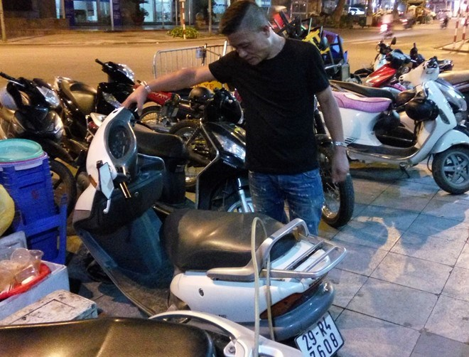 Dinh Thi Minh Phuong's husband stands next to the scooter, which was stolen in 2000 and returned to its owner on July 13, 2016. Photo credit: Hoang Lam/Zing News