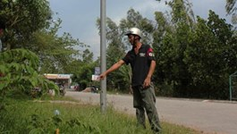 Ngo Trong Thien points at the light pole where he witnessed Danh Chiec's death in 2012. Photo credit: Lao Dong