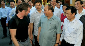 Prime Minister Nguyen Xuan Phuc talks with a foreign tourist in Hoi An on August 8. Photo credit: Quang Hieu/VnExpress