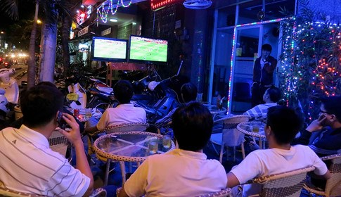 People watching football on a sidewalk cafe in Hanoi. Photo: Ngoc Thang