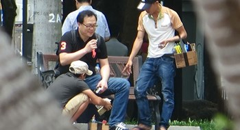 Two men polishing shoes for a foreign tourist in HCMC. Photo: Trac Rin