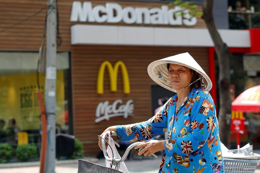 A woman wearing traditional conical hat pushes her bicycle past a restaurant. Photo: Reuters