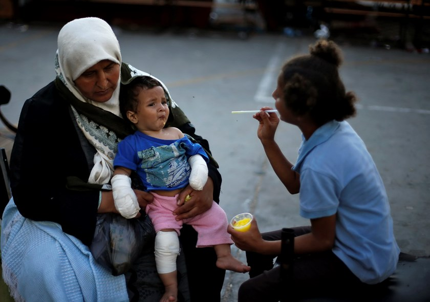A Palestinian woman holds a wounded boy at a United Nations-run school sheltering displaced Palestinians from the Israeli offensive, in Beit Lahiya town in the northern Gaza Strip August 12, 2014. Photo: Reuters