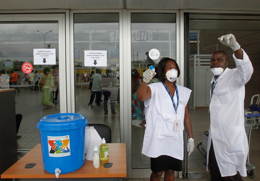 Health workers wearing protective masks and gloves gesture as they talk at the Felix Houphouet Boigny international airport in Abidjan August 12, 2014. Photo: Reuters