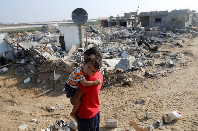 A Palestinian boy carries his brother next to the remains of their house, which witnesses said was destroyed in the Israeli offensive, during a 72-hour truce in Khan Younis the southern Gaza Strip August 13, 2014. Photo: Reuters