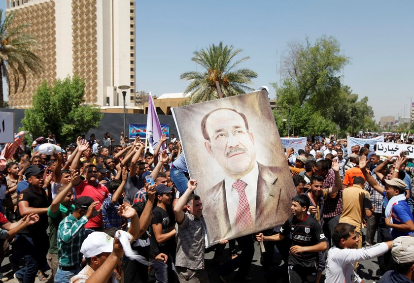 People carry portraits of Nuri al-Maliki as they gather in support of him in Baghdad August 13, 2014. Photo: Reuters
