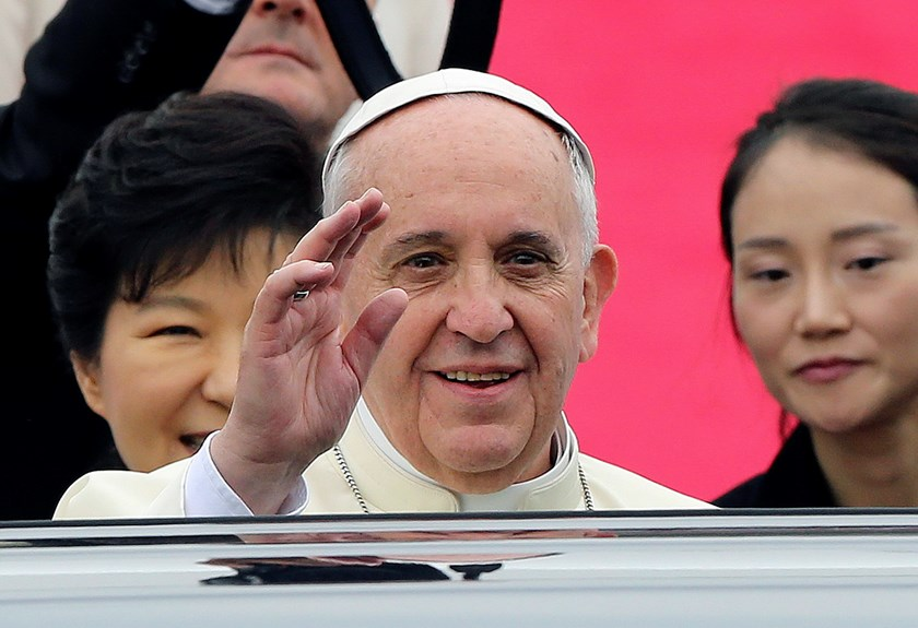 Pope Francis waves upon his arrival at Seoul Air Base as South Korean President Park Geun-hye (partly hidden L) looks on in Seongnam August 14, 2014. Photo: Reuters