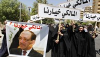 People hold a portrait of Nuri al-Maliki and signs as they gather in support of him in Baghdad August 13, 2014