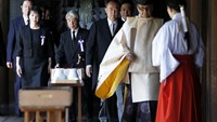 A group of members of the lower house of parliament walk down a hallway as they leave after offering prayers at the Yasukuni Shrine in Tokyo on Friday, Aug. 15, 2014.