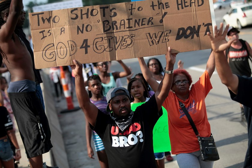 Demonstrators holds their signs and hands in the air as they protest against the shooting death of Michael Brown in Ferguson, Missouri August 18, 2014. Photo: Reuters