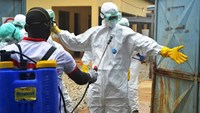 Guinea's Red Cross health workers wearing protective suits prepare to carry the body of a victim of Ebola at the NGO Medecin sans frontieres Ebola treatement centre near the hospital Donka in Conakry on Sept. 14, 2014.