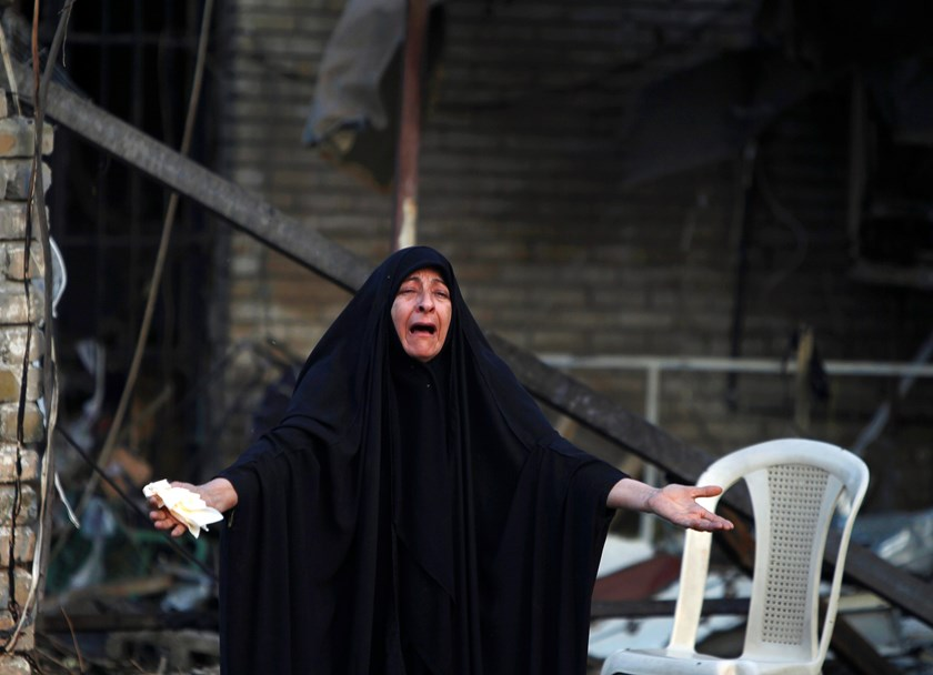 A woman reacts at the site of Tuesday's car bomb attack by Islamic State, at the entrance to the neighbourhood of Kadhimiya in Baghdad, October 15, 2014. Photo: Reuters