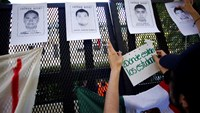 "A demonstrator places a sign that reads, ""Where are the students?"" next to pictures of some of the 43 missing students of the Ayotzinapa teachers' training college over a police fence outside Mexico's embassy in Buenos Aires October 22, 2014. Photo: Reute"