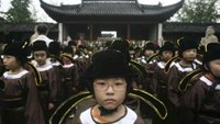 Pupils in traditional costumes attend a ceremony at a Confucius temple in Nanjing, Jiangsu province August 31, 2009. New school starters from a primary school took part in the ceremony marking the beginning of their studying age. Photo: Reuters