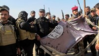 Iraqi Shiite fighters hold an Islamist State flag, which they pulled down from the frontlines after taking control of Saadiya in Diyala province from Islamist State militants, November 24, 2014. Photo: Reuters/Stringer