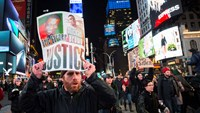 Protesters shout slogans as they demand justice for the death of Eric Garner, while waving placards through Times Square in the Manhattan borough of New York December 3, 2014. Thousands of protesters shouted at police and clogged streets of Manhattan on W