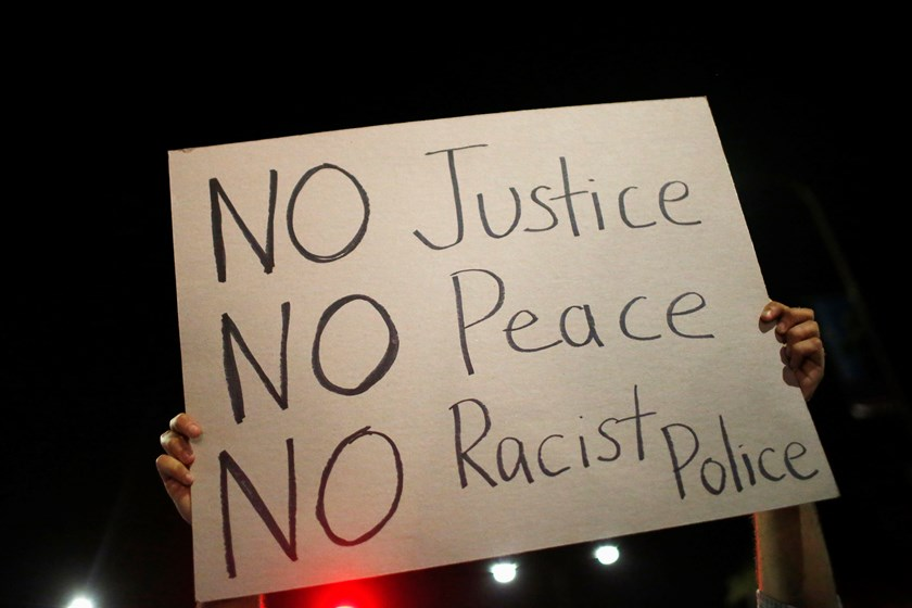 A protester holds a sign during a march against the New York City grand jury decision to not indict a police officer in the death of Eric Garner in Berkeley, California December 7, 2014.U.S. West Coast cities were braced for trouble on Sunday, after a nig