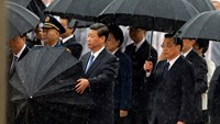 China's President Xi Jinping brings down his umbrella next to Premier Li Keqiang (R) before they and other Chinese Communist Party top leaders stand in silent tribute as it rains during a tribute ceremony at the Monument to the People's Heroes, on the 64t