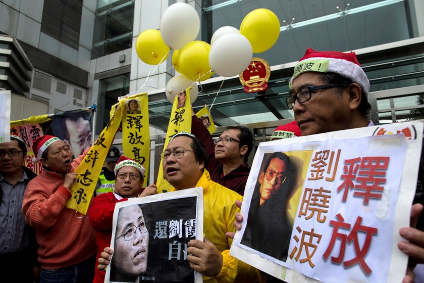 Pro-democracy protesters hold signs and posters of jailed Chinese Nobel Peace Prize laureate Liu Xiaobo (R) and his wife Liu Xia (C) during a protest outside the Chinese liaison office in Hong Kong December 25, 2014. Protesters on Thursday called for the