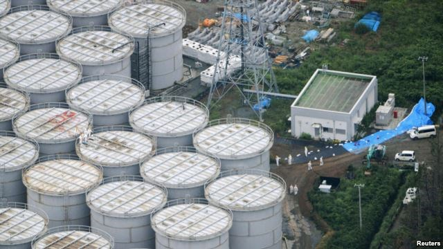 An aerial view of workers wearing protective suits and masks working atop contaminated water storage tanks at the Fukushima Daiichi nuclear power plant.