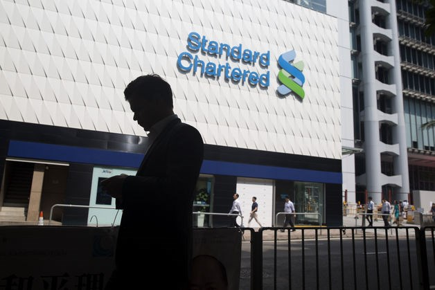 A pedestrian walks past a Standard Chartered Plc bank branch in the Central business district of Hong Kong, China. Photo: Brent Lewin/Bloomberg