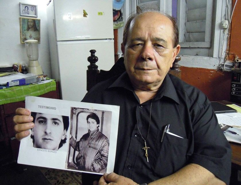 Raul Borges, 74, holds a picture of his son Ernesto Borges in his house in Havana January 2, 2015. Ernesto Borges, a KGB-trained counter-intelligence officer, has been in a Cuban prison for 16 years for attempting to hand over secrets to a U.S. diplomat i