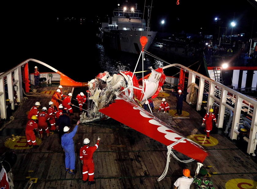 A section of the tail of AirAsia Flight QZ8501 passenger plane is seen on the deck of the rescue ship Crest Onyx, a day after it was lifted from the seabed, as crew try to lift it off the ship in Kumai Port, near Pangkalan Bun, Central Kalimantan January
