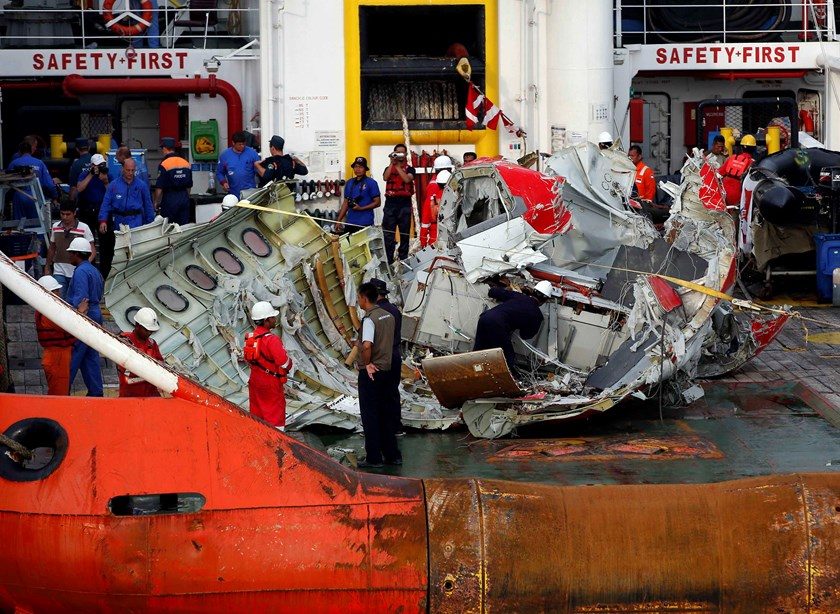 A section of the tail of AirAsia QZ8501 passenger plane is seen on the deck of the ship Crest Onyx, the day after it was lifted from the seabed, as it arrives at Kumai Port, near Pangkalan Bun, central Kalimantan January 11, 2015. REUTERS/Darren Whiteside