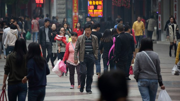 Shoppers and pedestrians walk along a shopping street in Wuhan, China. hotographer: Tomohiro Ohsumi/Bloomberg