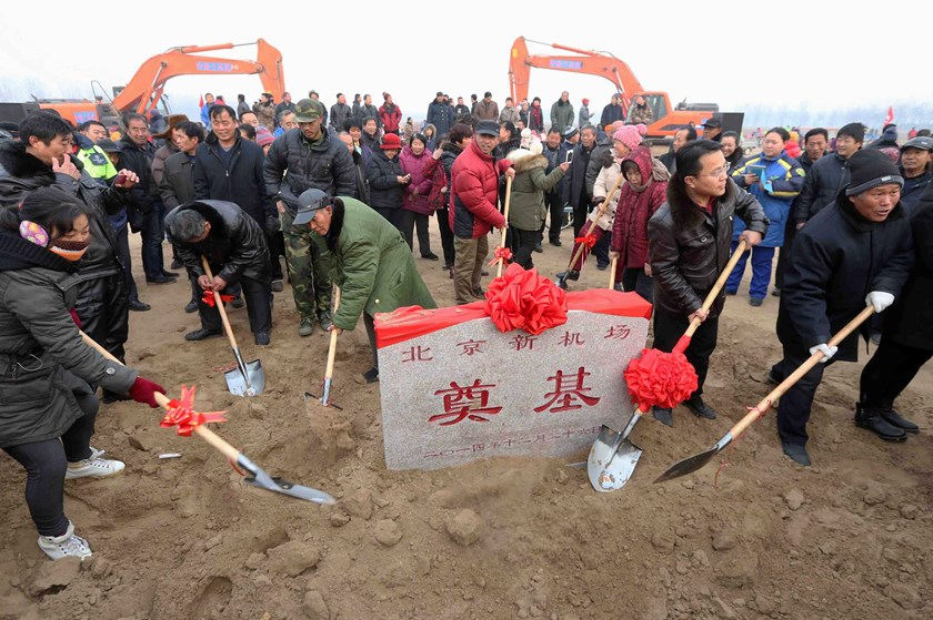 Locals pose for photographs with shovels and the cornerstone of Beijing's new airport after a ceremony on the outskirts of Beijing December 26, 2014. Photo: Reuters