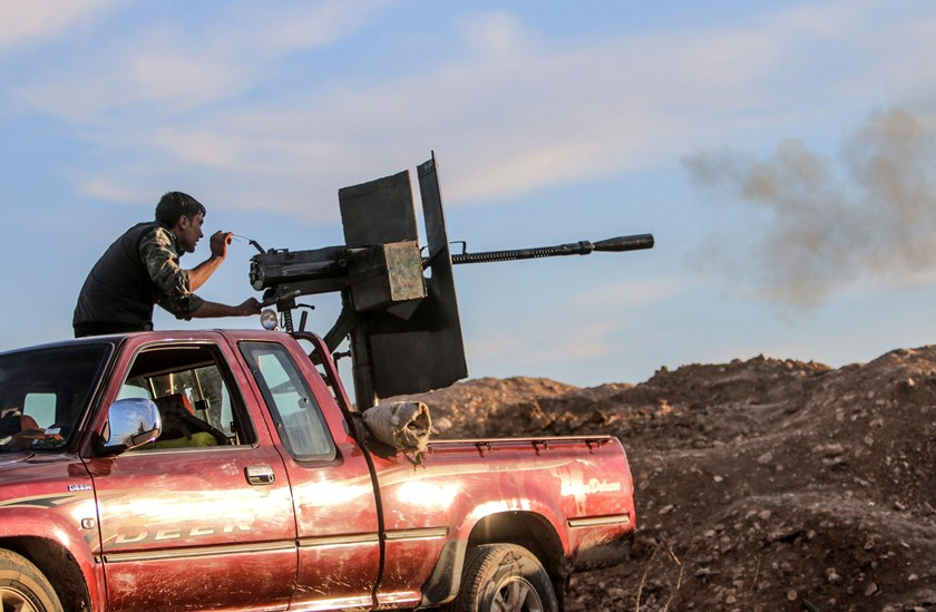 A Kurdish People's Protection Units (YPG) fighter fires a weapon installed at the back of a pickup truck during clashes with Islamic State fighters on a frontline in the southern Ras al-Ain countryside January 19, 2015. Picture taken January 19, 2015. REU