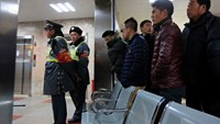 Security guards stand in front of family members as they wait at a hospital after a stampede during a New Year's celebration on the Bund, a waterfront area in central Shanghai January 1, 2015. REUTERS/Aly Song