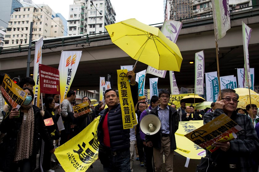 "Pro-democracy protesters hold up yellow umbrellas, symbols of the Occupy Central movement, and banners reading ""I want real universal suffrage"" during a march in the streets to demand universal suffrage in Hong Kong February 1, 2015.  REUTERS/Tyrone Siu"