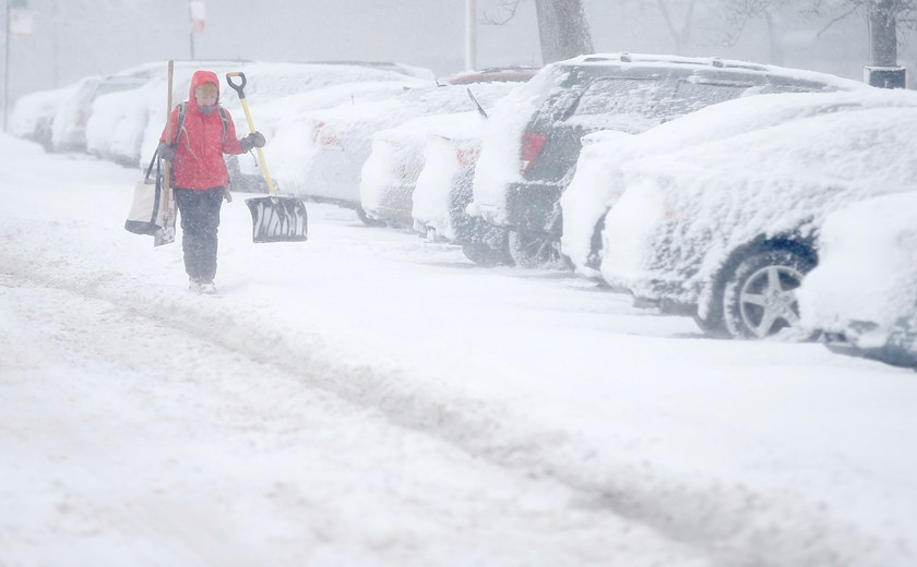 A woman carries a shovel through a parking lot during blizzard conditions in Chicago, Illinois, February 1, 2015. REUTERS/Jim Young