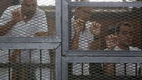 Al Jazeera journalists (L-R) Mohamed Fahmy, Peter Greste and Baher Mohamed stand behind bars at a court in Cairo in this May 15, 2014 file photo. Greste was released from a Cairo jail on February 1, 2015 and left Egypt after 400 days in prison on charges