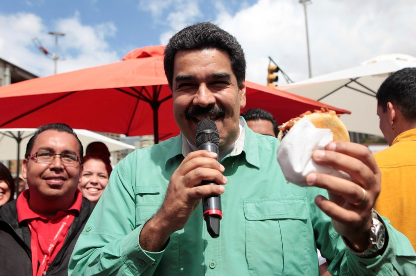 Venezuela's President Nicolas Maduro eats a traditional arepa while visiting a market in downtown Caracas January 24, 2015. REUTERS/Miraflores Palace/Handout via Reuters