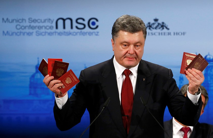 Ukraine's President Petro Poroshenko holds Russian passports to prove the presence of Russian troops in Ukraine as he addresses during the 51st Munich Security Conference at the 'Bayerischer Hof' hotel in Munich February 7, 2015. REUTERS/Michael Dalder