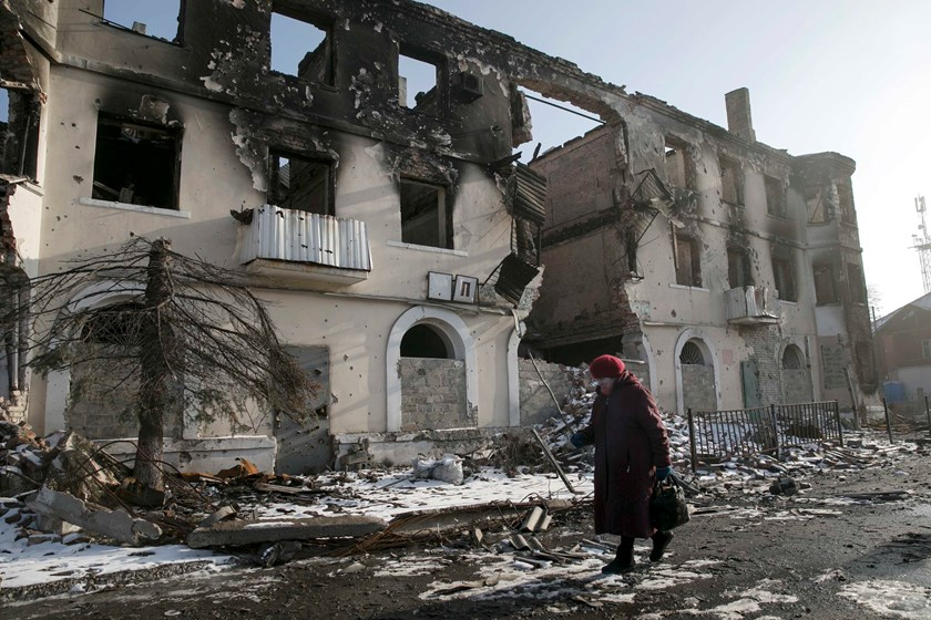 A woman walks past a damaged building in the town of Vuhlehirsk near Donetsk, Ukraine, February 14, 2015. Fighting intensified in eastern Ukraine on Saturday as separatist rebels tried to seize more territory before a ceasefire takes effect at midnight, t