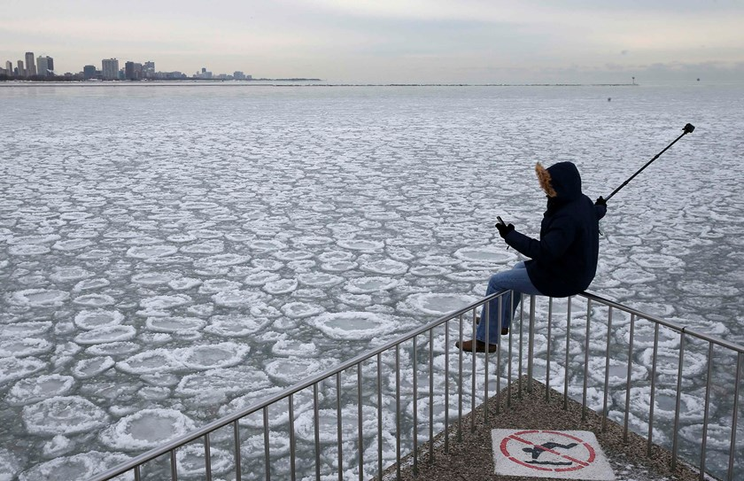 Charles Martinez sits on a railing to take a selfie overlooking the partially frozen Lake Michigan in Chicago, Illinois, in this January 5, 2015 file photo. REUTERS/Jim Young/Files