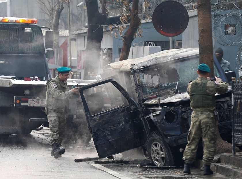 Turkish soldiers take pictures of a vehicle at the site of a suicide attack in Kabul February 26, 2015. A suicide bomber rammed a vehicle laden with explosives into a Turkish embassy car in the Afghan capital on Thursday, killing at least one person insid