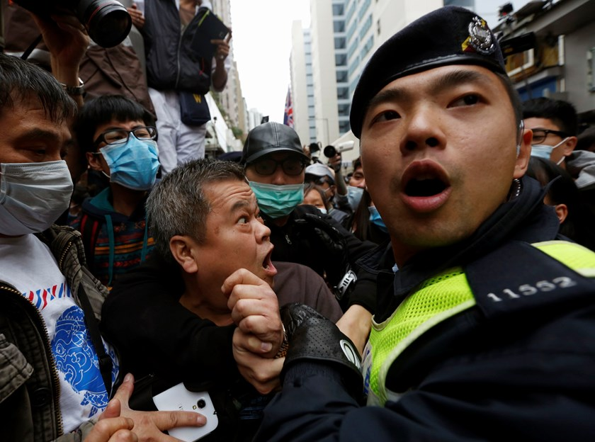 A Yuen Long resident is taken away by a policeman during a confrontation with masked protesters, who are demonstrating against mainland traders, at Yuen Long district near the border with mainland China in Hong Kong March 1, 2015. The protest on Sunday wa
