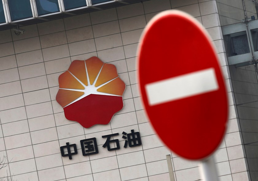 The logo of PetroChina is seen behind a traffic sign at its headquarters in Beijing March 17, 2015. REUTERS/Kim Kyung-Hoon