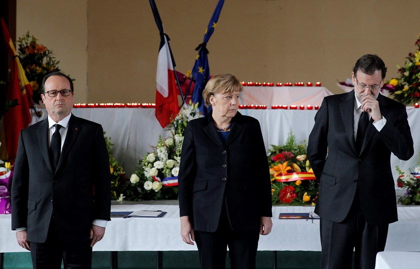 French President Francois Hollande (L), German Chancellor Angela Merkel (C) and Spain's Prime Minister Mariano Rajoy pay respect to the victims at the makeshift morgue prepared for the 150 victims who died in a Germanwings Airbus A320 plane crash in the F