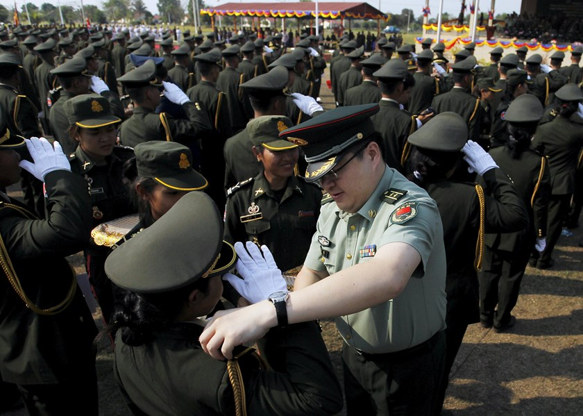 A Chinese army advisor (C) puts rank on Cambodian army graduates during a graduation ceremony at Army Institute in Kampong Speu province March 12, 2015. Photo: Reuters